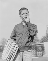 USA, New York, New York City, Paperboy (14-15) holding newspapers, shouting